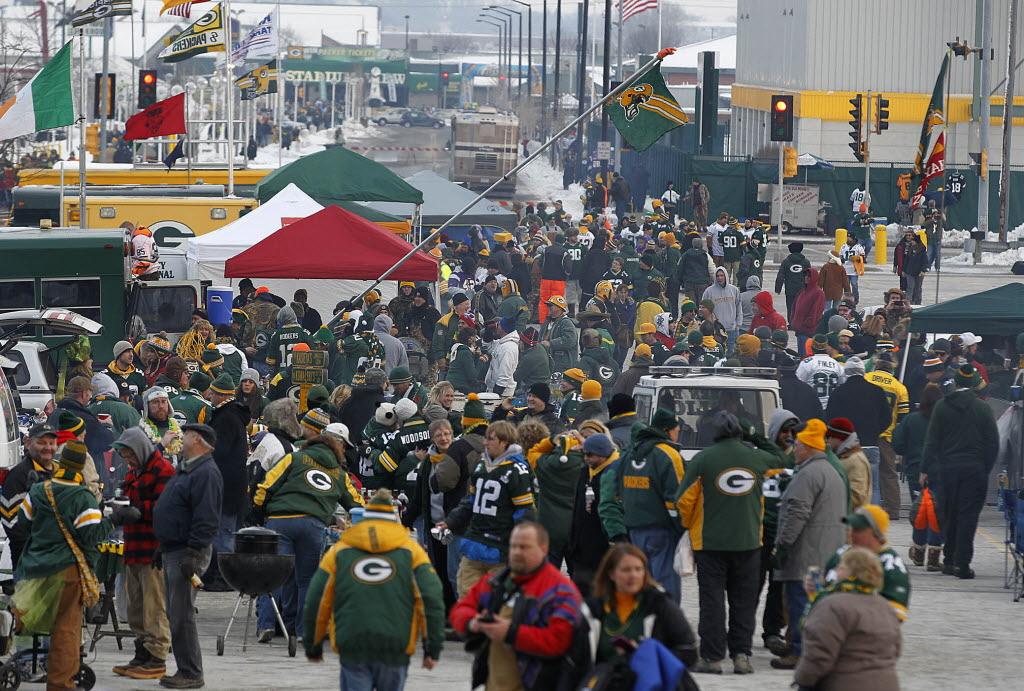 726801 bytes; 2079 x 1404; Packer and Viking fans fill the parking area tailgating as a Packer fan raises a flag before the NFL